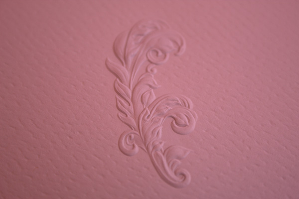 An emboss floral print on textured rose colored paper